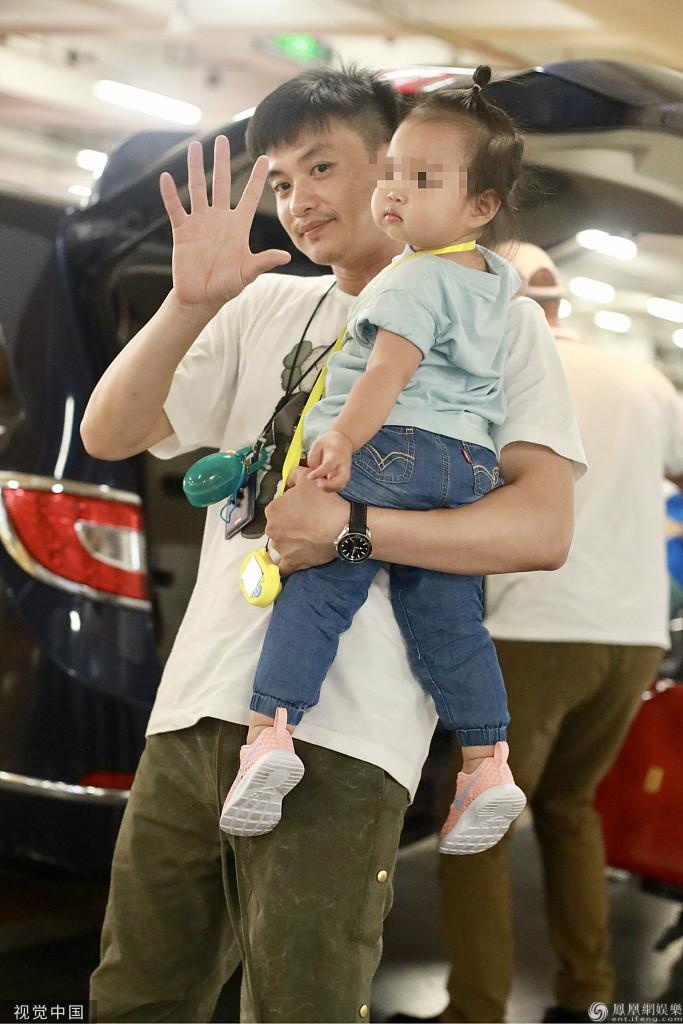 周一围抱女儿现身机场 对镜挥手气质柔和